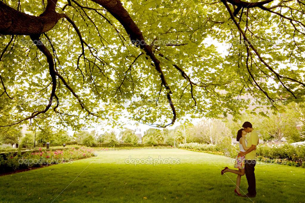 Couple kissing under tree