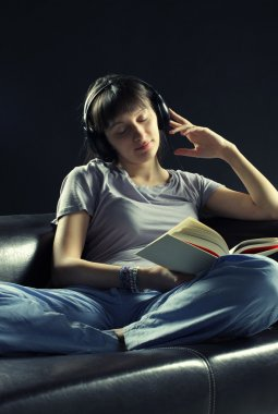 Relaxed young woman listening music and reading a book