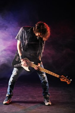 Rock bassist plays his bass on a dark background
