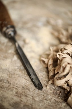 A work table of a carpenter with a gouge and a pile of wood chip