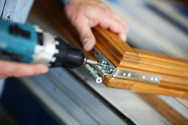 Hands of a carpenter screwed a hinge on a wooden door