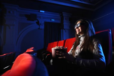Portrait of a beautiful girl with 3D glasses, in a empty movie t