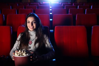 A pretty girl alone sitting in a empty movie theater, she eats p
