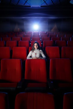 Beautiful young woman alone sitting in a empty movie theater