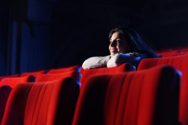 Watching a movie at the cinema: portrait of a pretty girl in a m