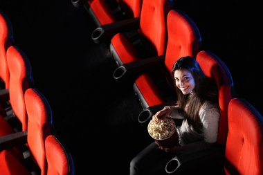 A pretty young woman sitting in an empty theater, eats popcorn a