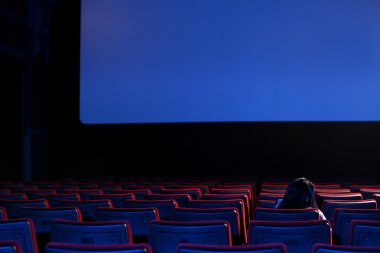 The end: youn woman alone sitting in a empty movie theater,rear