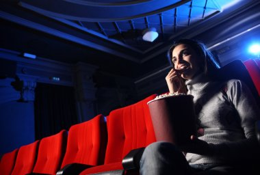 A pretty young woman sitting in an empty theater, she eats popco