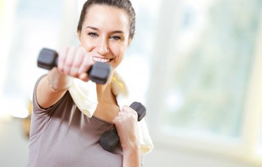Dumbbell in hand of working out young smiling female stock vector