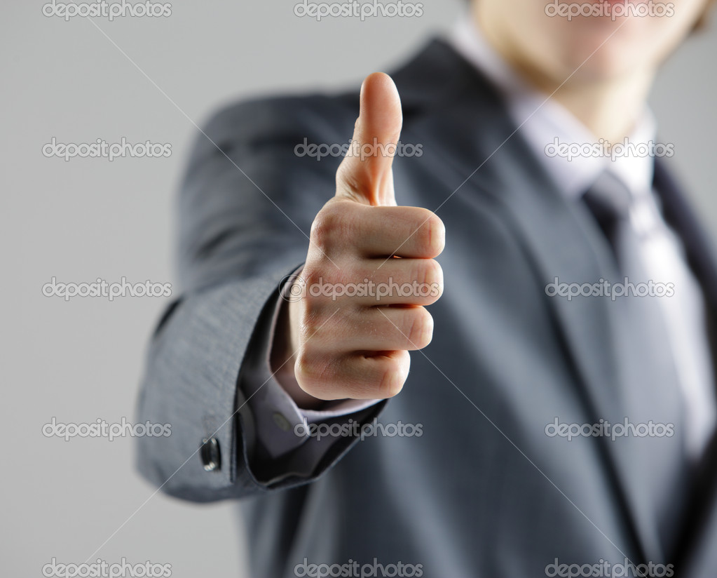 Close-up of a young businessman showing thumbs up.