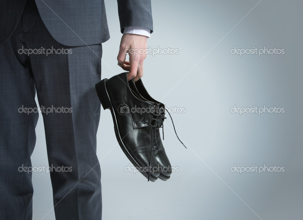 Businessman holding the shoes in hand, close up