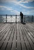 Fotografie mladý muž hledá do vzdálenosti, pobřeží, brighton, pier