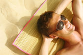 a strandon napozással ember
