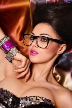 Fashion portrait of beautiful brunette girl model in glasses with birght makeup pink lips and unusual haistyle bright colorful background