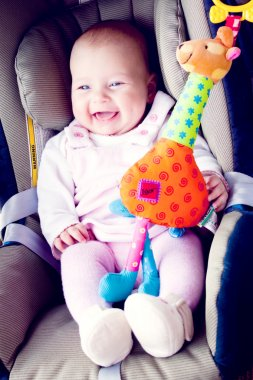 Baby girl smile in carseat