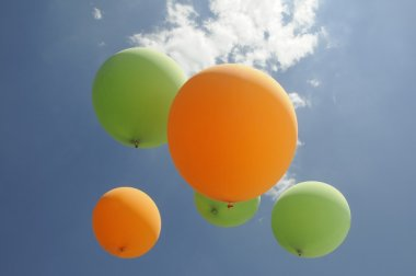 Green and orange air balloons hover towards the sun