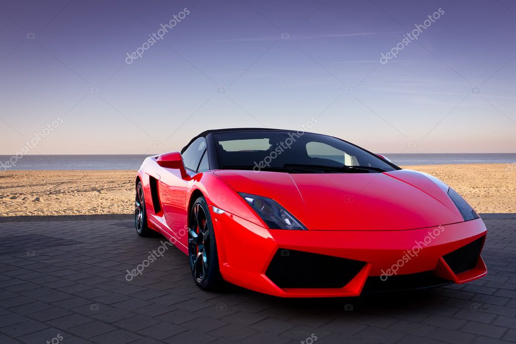 Red sports car at sunset beach