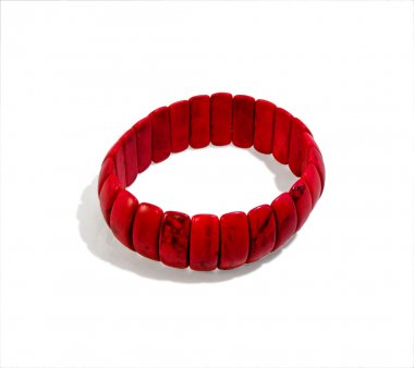 Bright red bracelet composed of oblong stones. Isolated, close-u