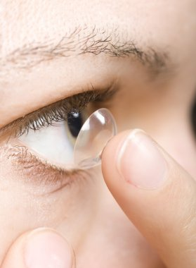 Woman inserting a contact lens into the eye