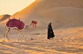 jezdec na velbloudu v černém s velbloud v poušti
