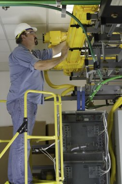 Telecommunication Switch Worker Inspecting Fiber Optic Run