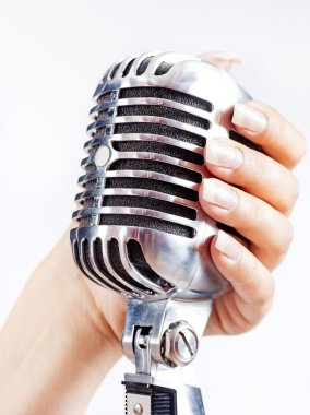 Big retro microphone in woman's hand