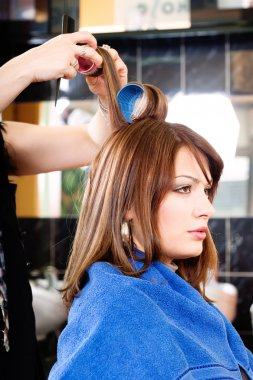 Hairdresser putting rollers on hair