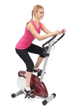 Young woman doing indoor biking exercise