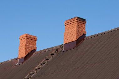 Bricks chimney on the dark metal-sheet roof stock vector