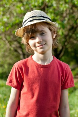 The fair-haired boy in red shirt and hat