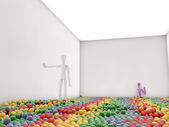 Dummies in a white room with colored balls on the floor