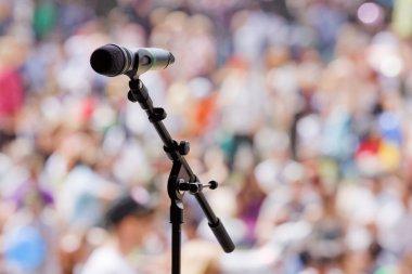An open microphone awaits the next act at a summer music festival stock vector
