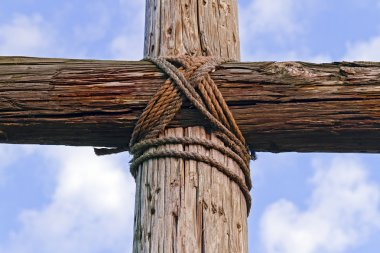 Closeup of a rugged wooden Cross and blue, cloudy sky
