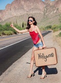 mladá žena stopem na opuštěné pouštní silnice