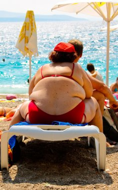 Obese woman sitting on deck chair on beach in Croatia