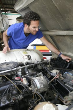 Young man doing mechanical work on car engine