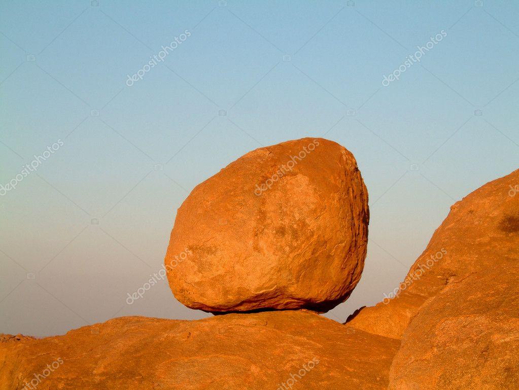 Huge granite boulder perched on rocks against blue sky