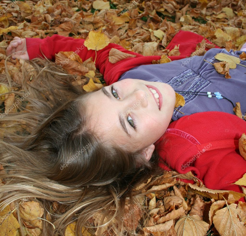 Young girl lying in autumn leaves