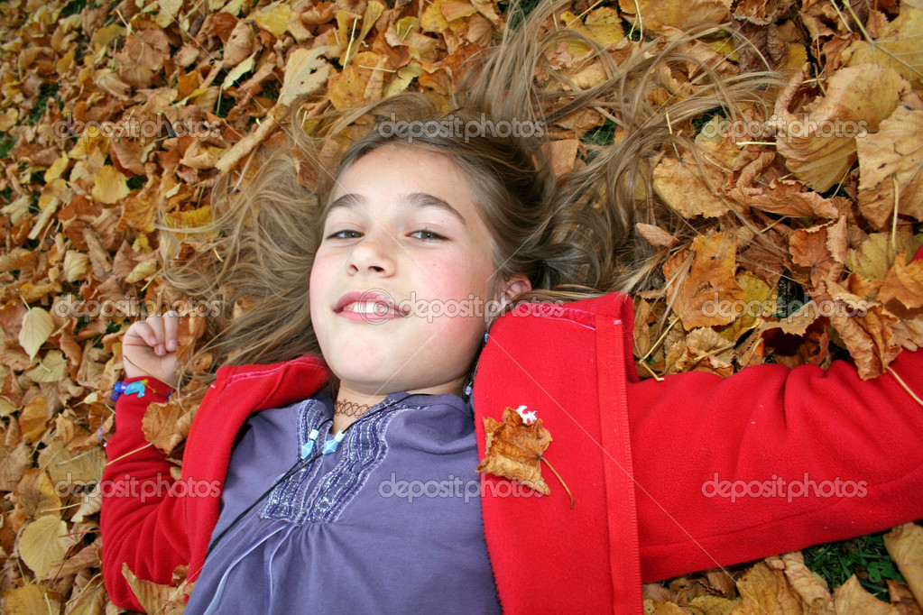 Close up young girl with hair in autumn leaves