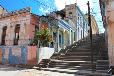 Long Padre Pico street staps with crumbling buildings in Santiago de Cuba