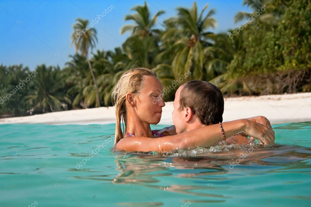 Portrait of attractive couple having fan on the tropical beach