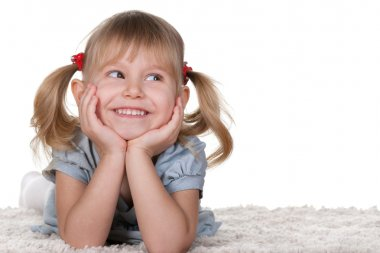 Cheerful little girl lying on the carpet