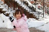 kleines Mädchen wirft einen riesigen Schneeball