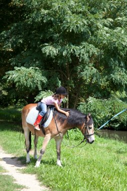 Little girl petting a horse while horseback riding
