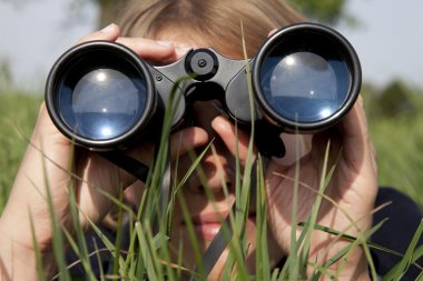 Woman with binoculars is discovering the surrounding