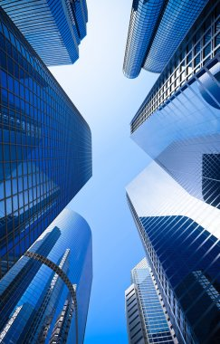 Street of highrise glass skyscraper buildings low angle shot in blue dominant against a clear sky stock vector