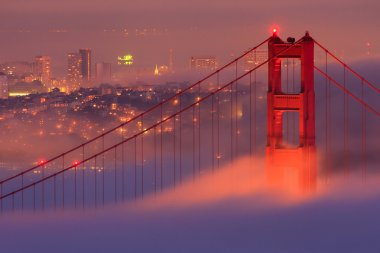 Golden Gate Bridge glowing in covering fog after sunset. stock vector