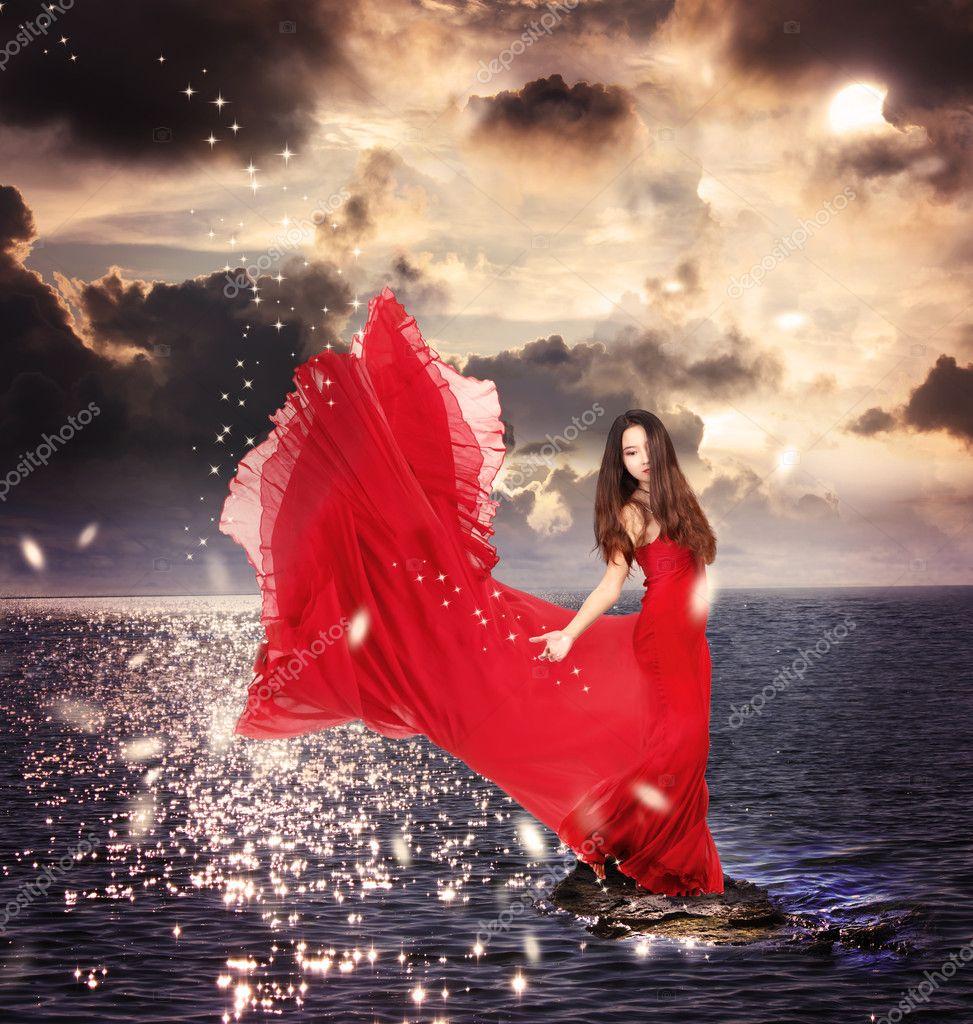 Girl in Red Dress Standing on Ocean Rocks