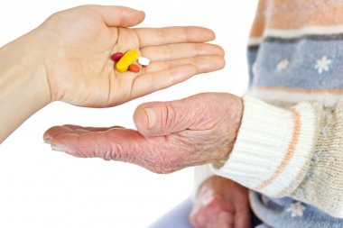 Giving pills to elderly woman