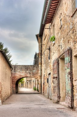 Old narrow alley with arch in tuscan village - antique italian lane in San Quirico d'Orcia, Siena, Tuscany, Italy - hdr image stock vector
